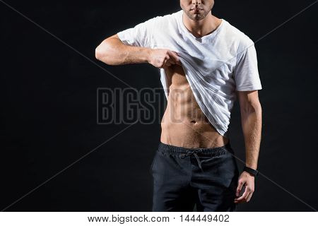 Fit young man is showing his trained abdomen. He is standing and raising t-shirt. Isolated and copy space in left side