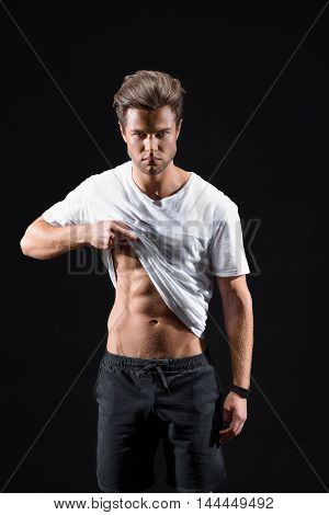 Confident young man is raising t-shirt and showing abdomen press. He is standing and looking at camera with seriousness. Isolated