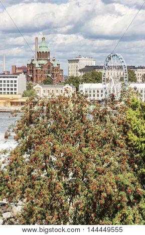 Church and a ferries wheel behind rowan tree in Helsinki Finland