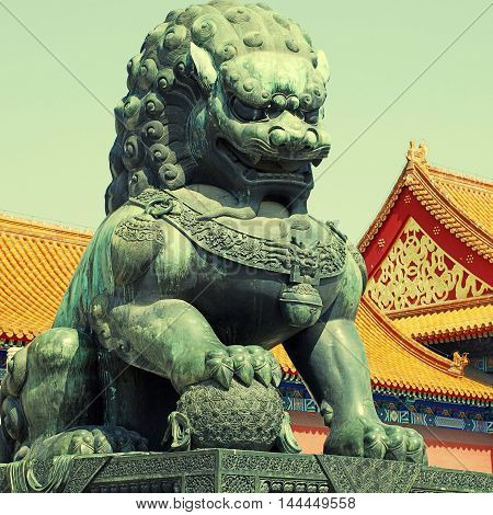Ancient bronze lion and red chinese pavilliones in Emperor Forbidden city(Beijing, China), square toned image