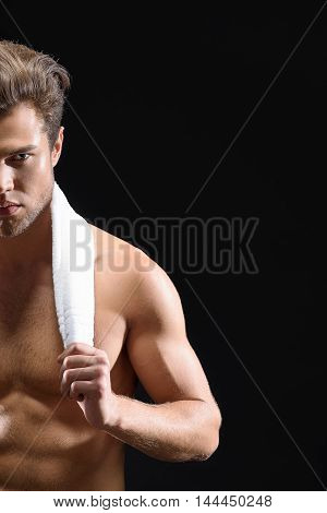 Half portrait of handsome young man holding towel over his neck. He is standing and looking at camera with desire. Isolated on black background