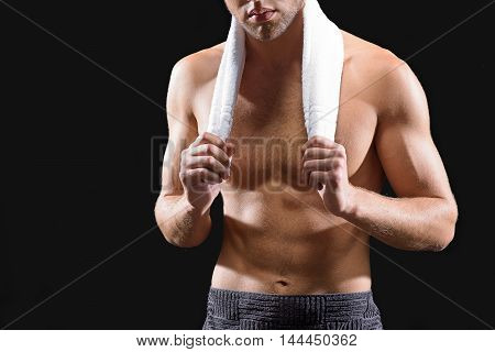 Fit young man is wiping body with towel after shower. He is standing with naked muscular torso. Isolated and copy space in left side