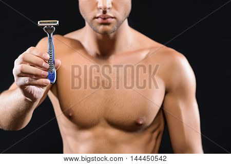 It is time to shave my stubble. Confident young man is standing and holding razor. Isolated