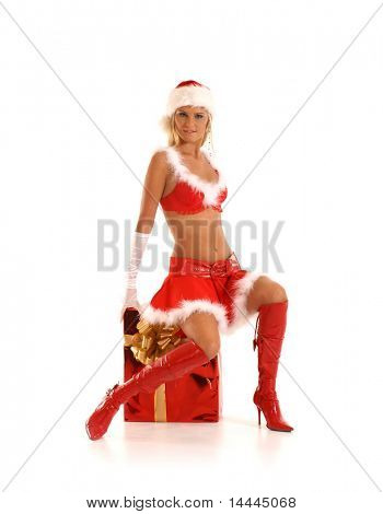 Young sexy Santa sitting on a big present isolated on white