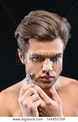 Young man is shaving his stubble. He is standing and looking forward with concentration. Isolated