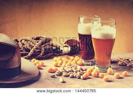 Glasses of beer, rope, cheese balls,empty bottle and pistachio nuts