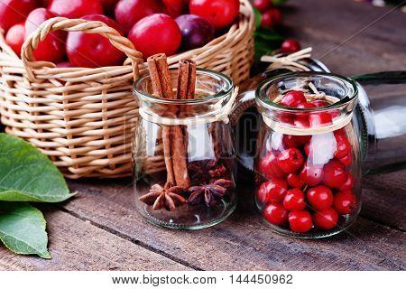 Plums in a basket and jar with rowanberry