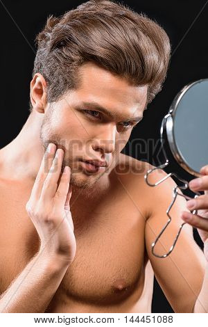 Handsome young man is touching his stubble and looking at mirror pensively. He is standing with naked torso