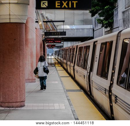 Woman waiting for BART (Bay Area Rapid Transit) train in Colma CA.