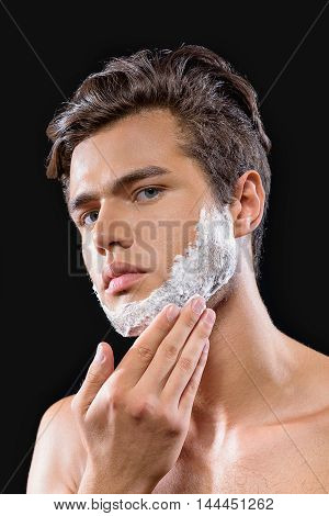 Pensive young man is applying shaving foam on his chin. He is standing and looking forward with confidence. Isolated
