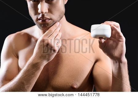 Handsome young man prefers skincare treatment. He is standing and holding cream jar. Guy is touching his chin pensively. Isolated