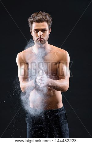 Sexy young man is applying white chalk on hands before training. He is standing and looking at camera with confidence. Isolated