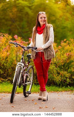 Fall lifestyle concept harmony freedom. Beauty young woman fashion girl relaxing in autumnal park with bicycle outdoor