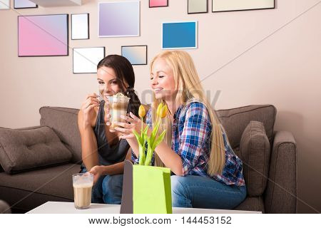 Two girlfriend siting on a sofa and enjoying coffee in a coffee shop.