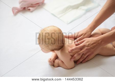 Useful motion. Top view of mother hand doing massage for baby, lying on stomach on diaper