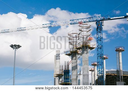 construction company builds a stadium for football competitions. Cranes against a background of the sky. Concrete columns and reinforcement mesh.