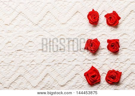 Valentines day wedding invitation or greeting card. Red decorative satin rose flowers on white cloth lace background