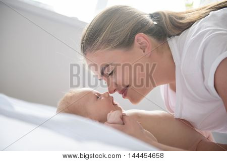 Tender moments of happiness. Close up of happy smiling mother playing with her cute baby in bedroom