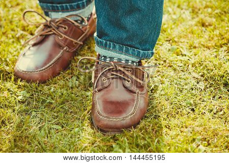 Clothing boots shoes fashion concept. Male footwear in grass. Lower part of legs in jeans and moccasin boots.