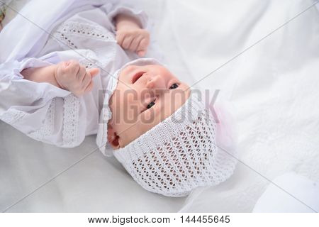 Looking at you. Portrait of adorable baby girl lying down on blanket and wearing in knitted cap isolated on white