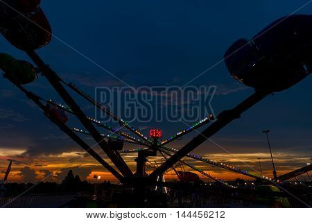 Amusement ride pictured at dusk against a pretty sunset sky