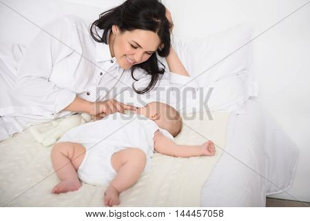 Tender moments with mother. Shot of loving mother checking her sleeping baby in bed and smiling