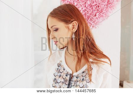 soft red-haired girl looking out the window. The concept of lifestyle