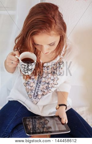 Girl looks in tablet and drinking tea. The concept of lifestyle
