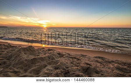 Summer Beach Background. The sunsets along a wide sandy beach with a water sunset background. Port Austin, Michigan.