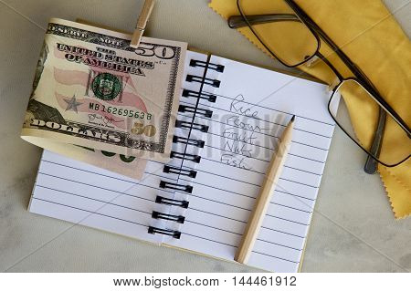 Shopping list with American dollars and spectacles.