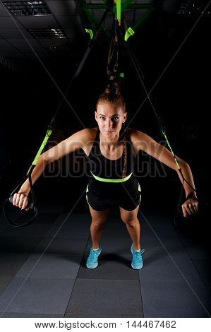 One women doing push ups training arms with trx fitness straps in the gym Concept workout healthy lifestyle sport