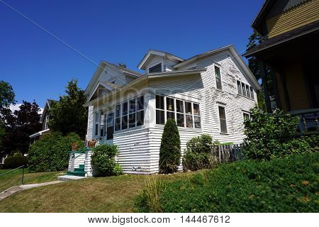 PETOSKEY, MICHIGAN / UNITED STATES - DECEMBER 5, 2016: A white home with an enclosed front porch and peeling paint near downtown Petoskey, Michigan.