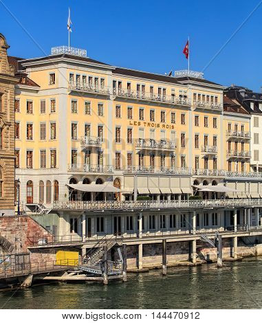 Basel, Switzerland - 27 August, 2016: Grand Hotel Les Trois Rois building facade, view from the Mittlere Bruecke bridge. Grand Hotel Les Trois Rois is a luxurious 5-star hotel, located on the left bank of the Rhine river in the Swiss city of Basel.