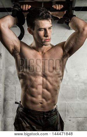 Athletic man posing with flexed muscles in doorway.