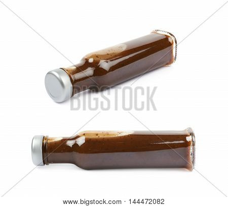 Glass bottle of barbecue bbq sauce lying on its side, composition isolated over the white background, set of two different foreshortenings