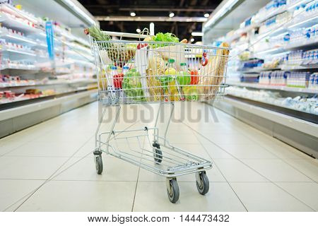 Consumer cart with products in supermarket