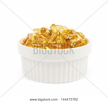 Ceramic bowl full of yellow softgel pills isolated over the white background