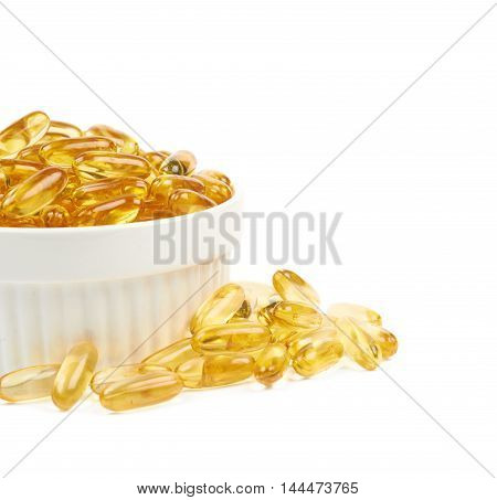 Ceramic bowl full of yellow softgel pills, close-up crop composition isolated over the white background