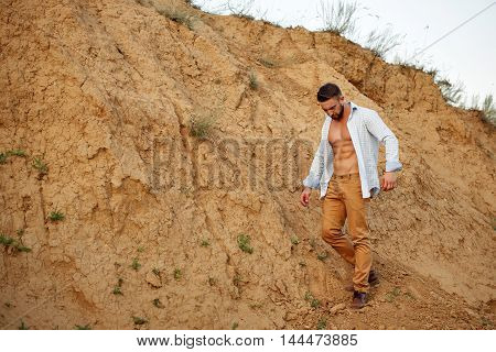 Young handsome man descends into a sand pit. A man in an unbuttoned shirt. It is evident muscular torso.
