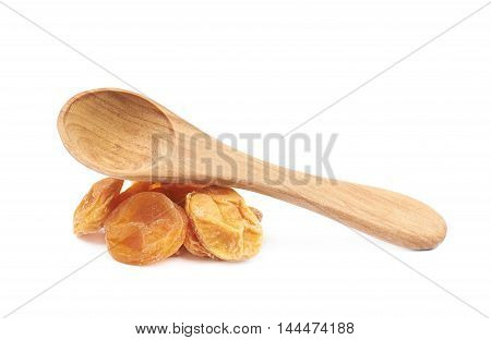 Pile of dried apricot fruits with a wooden spoon over it, composition isolated over the white background