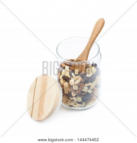Glass kitchen jar filled with the mix of nuts and dried fruits, composition isolated over the white background