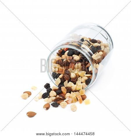 Knocked over glass kitchen jar filled with the mix of nuts and dried fruits, composition isolated over the white background