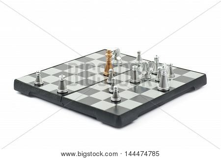 Chess board with the single silver king against full set of golden figures, composition isolated over the white background