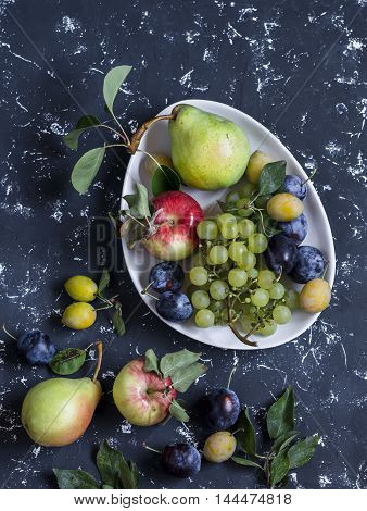 Fresh fruit - grapes pears apples plums on a dark background top view