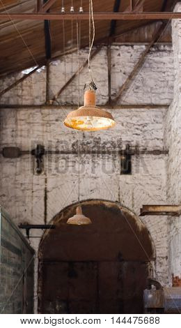 old rusty lamp hanging in an abandoned factory