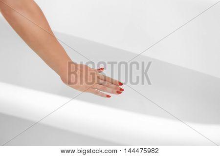 Female hand in water in bathroom