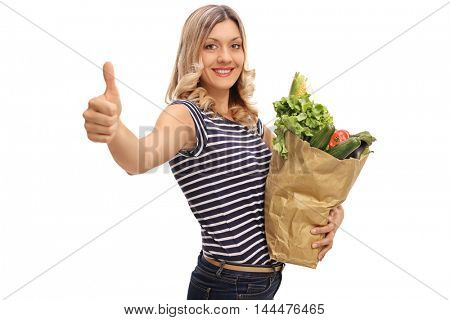 Smiling woman giving a thumb up and holding a bag of groceries isolated on white background