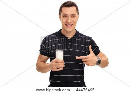 Cheerful man holding a glass of milk and pointing towards it isolated on white background