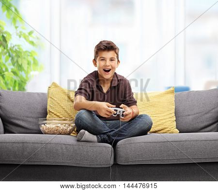 Happy kid playing video games and sitting on a sofa