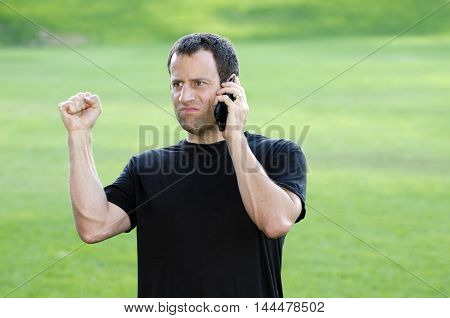 Frustrated angry man on his cell phone outdoors in a black t-shirt.
